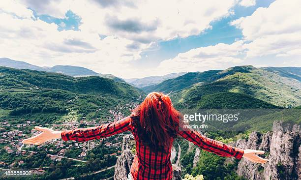 Girl with outstretched hands at the top of a mountain