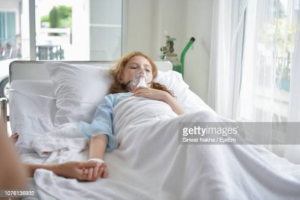 girl with oxygen mask on bed at hospital - breathing device stock pictures, royalty-free photos & images