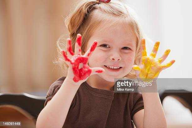 Girl (2-3) with paint covered hands
