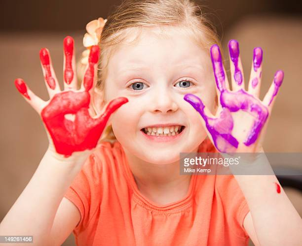 Girl (4-5) with paint covered hands