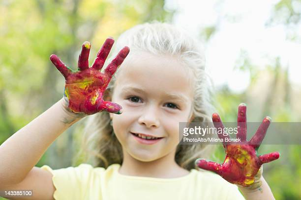 Girl with paint covered hands, portrait