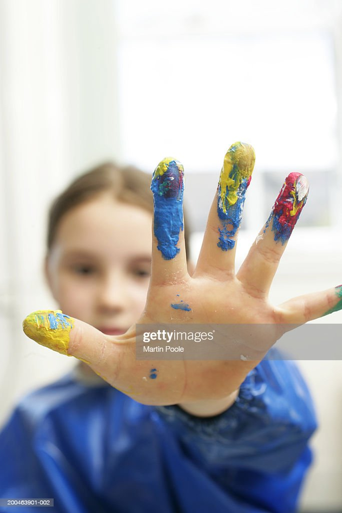 Girl (6-8) with paint on fingers, close up, portrait : Stock Photo