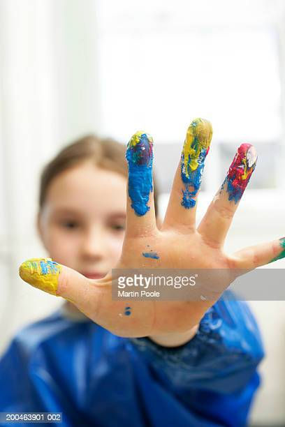 Girl (6-8) with paint on fingers, close up, portrait