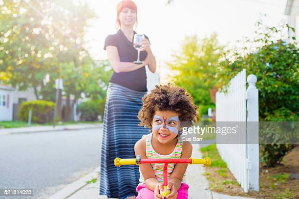 Girl with painted face crouching on scooter on suburban street