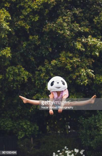 Girl with panda mask on doing gymnastics in backyard.