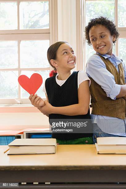 girl with paper heart and smiling boy in classroom - valentines african american stock pictures, royalty-free photos & images