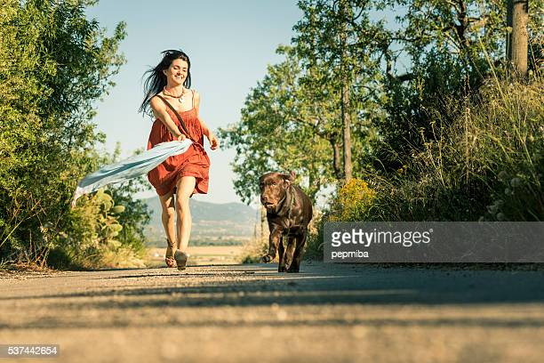Girl with pet dog walking along road in countryside