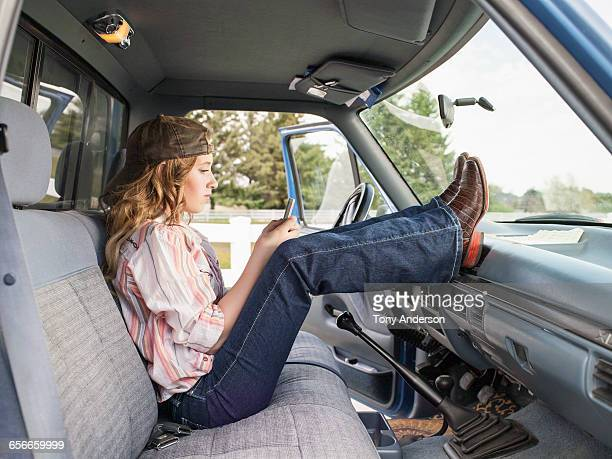 Girl with phone in pickup wearing cowboy boots