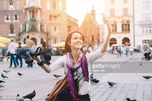 Girl with pigeons taking a selfie in Krakow