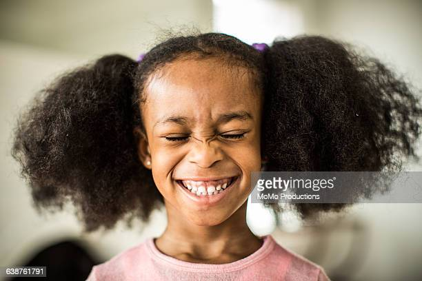 girl (6yrs) with pigtails smiling - 薄ピンク ストックフォトと画像