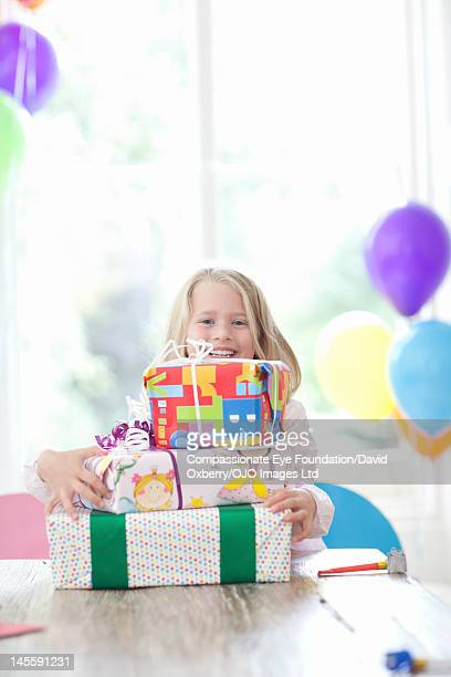 Girl (7-8) with pile of presents, smiling
