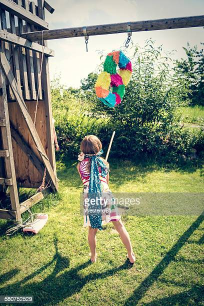 Girl with Pinata formed like an Eight in the garden