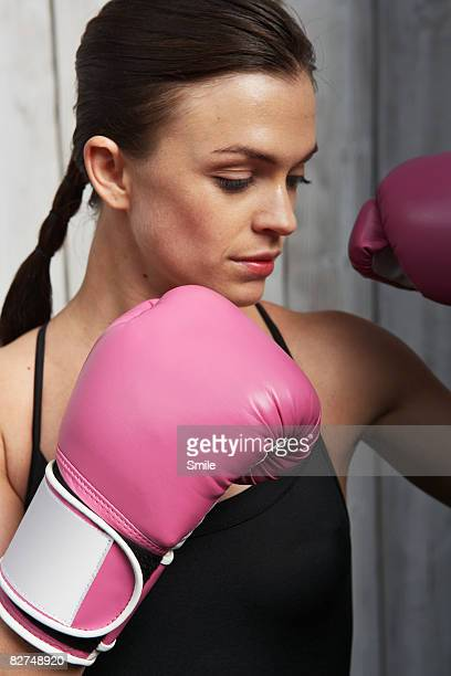 girl with pink boxing gloves, hands near face - women's boxing stock pictures, royalty-free photos & images