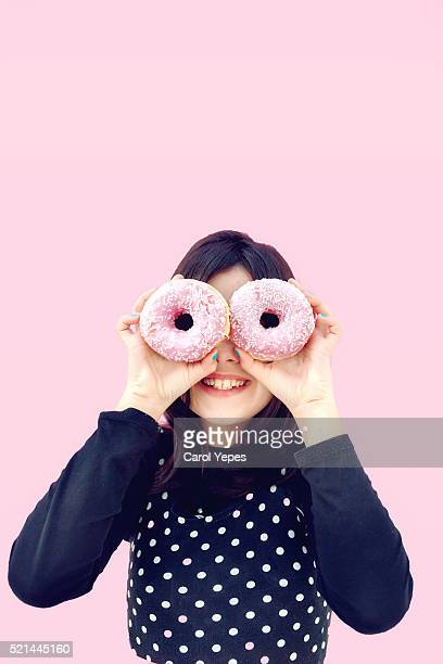 girl with pink donuts in front of her eyes - fat people eating donuts stock pictures, royalty-free photos & images
