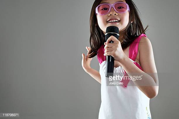 Girl with pink sunglasses singing and dancing