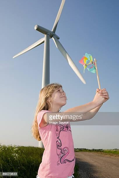 Girl with pinwheel by wind turbine