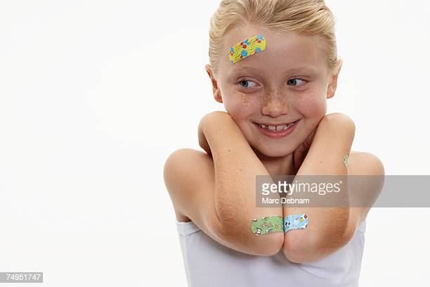Girl (7-9) with plasters on head and arms, smiling