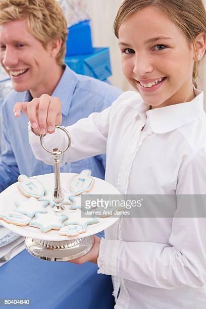 Girl with plate of Hanukkah cookies