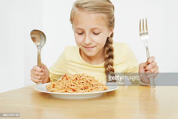 girl with plate of spaghetti and oversized cutlery - goldilocks stock photos and pictures