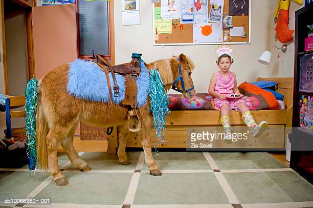 Girl (6-7) with pony in bedroom