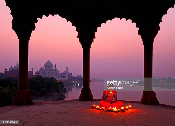 Girl with prayer lamp with Taj Mahal in background