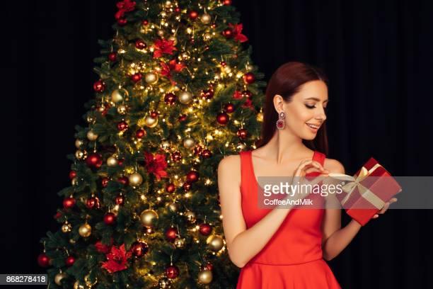 Fille avec présent en face de l'arbre de Noël
