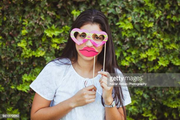 Girl with props on her face.