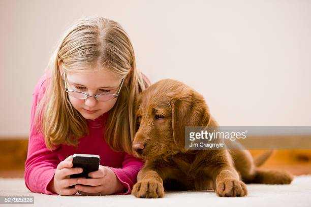 Girl (8-9) with puppy looking at cell phone