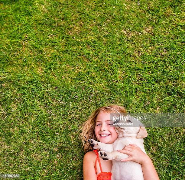 Mädchen mit Hund liegen auf Gras