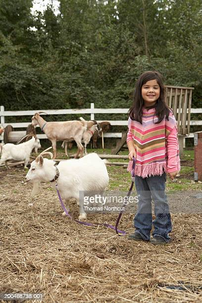 Girl (5-7) with pygmy goat on leash in pasture on farm, portrait