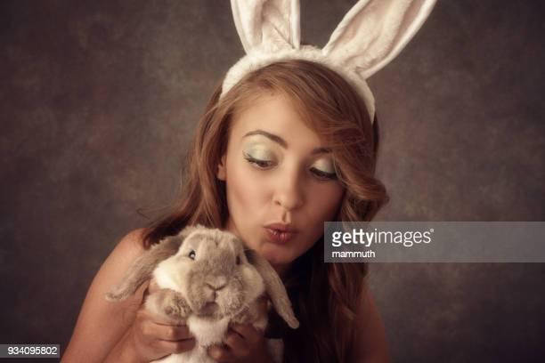 Mädchen mit Hasenohren spielen mit einem echten Hasen zu Ostern