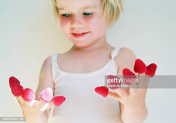 Girl (3-5) with rasberries on fingers, smiling