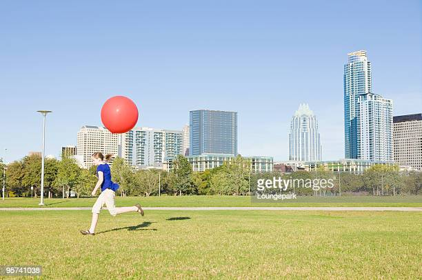 Girl with red balloon running through urban park