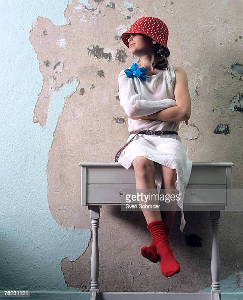 girl with red cap sitting on chest of drawers