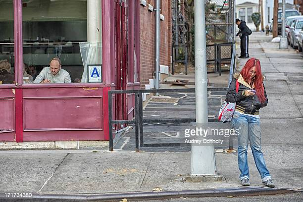 Girl with red hair stands on corner using cell phone.. Her hair matches the cafe on the left with an health department A in the window and a man...