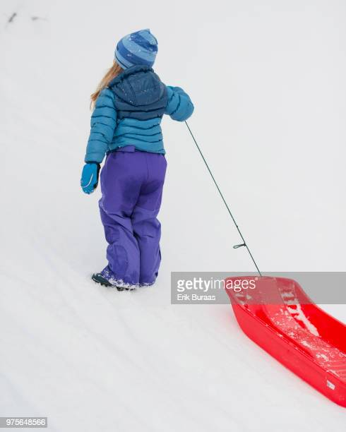 Girl with red plastic sledge in the snow