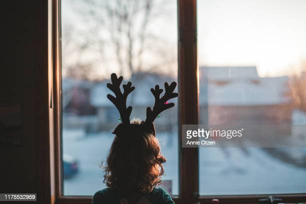girl with reindeer antlers window - solitude stock pictures, royalty-free photos & images