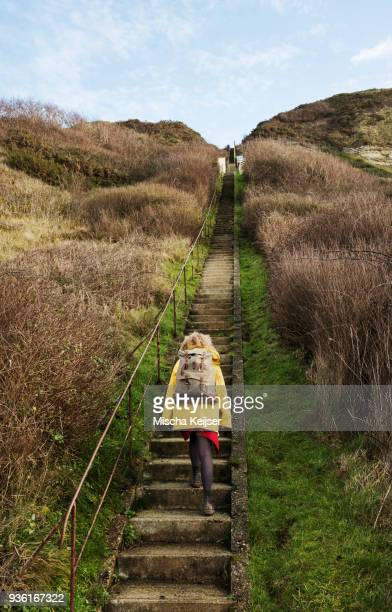 Girl with retro backpack moving up stairway near former NATO fuel station on Normandy coast