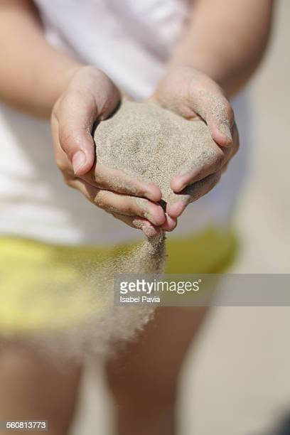 Girl with sand running through her hands
