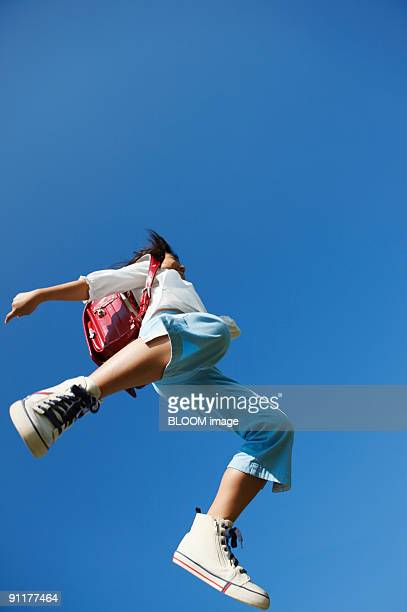 Girl with school satchel jumping, low angle view