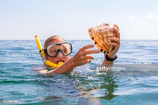 a girl with scuba mask holding a large sea shell - base equipamento desportivo imagens e fotografias de stock