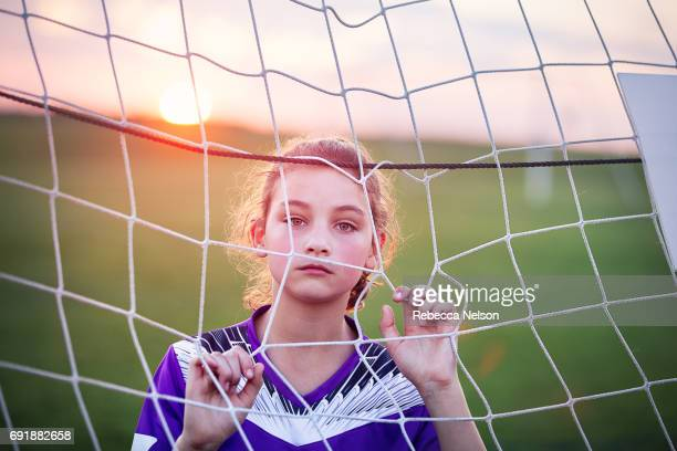 girl with serious expression looking through soccer goal net