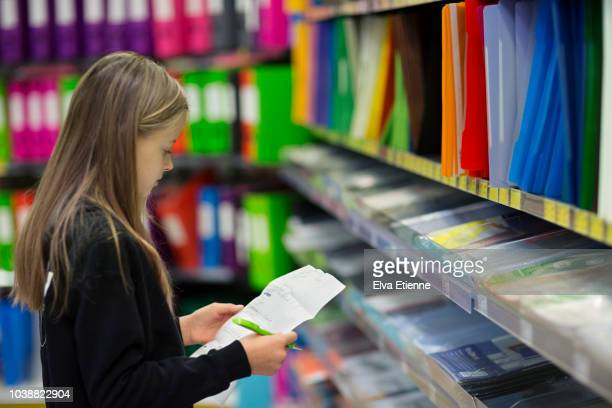 girl (10-11) with shopping list looking for 'back to school' items in a store - schulbedarf stock-fotos und bilder