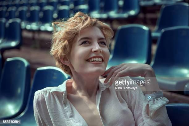 girl with short hair laughing at stadium tribune - frau bluse durchsichtig stock-fotos und bilder