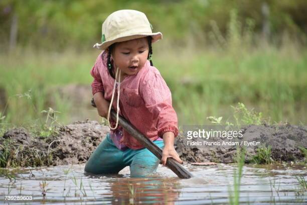 girl with shovel at rice paddy - francis spade photos et images de collection
