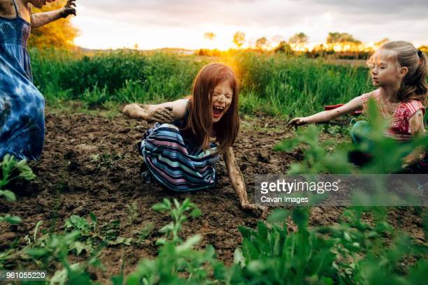 girl with sisters shouting while crouching in mud - dirty little girls photos stock pictures, royalty-free photos & images