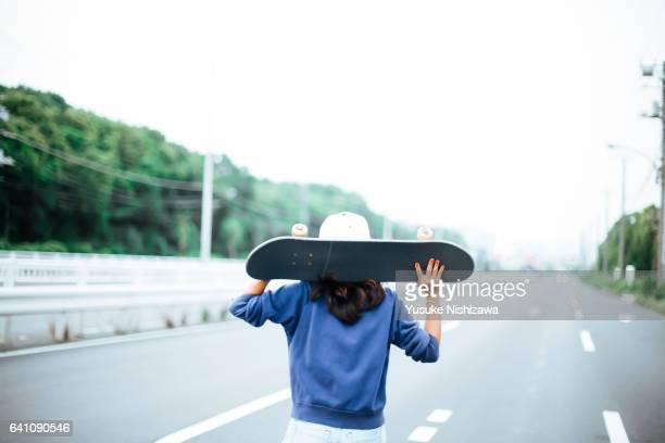 a girl with skateboard - yusuke nishizawa stock-fotos und bilder