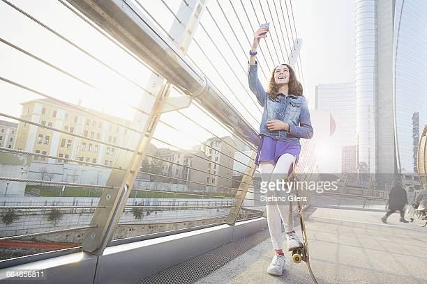 Girl with skateboard using smartphone to take selfie