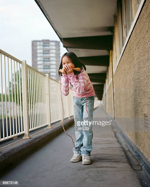 Girl with skipping rope on housing estate