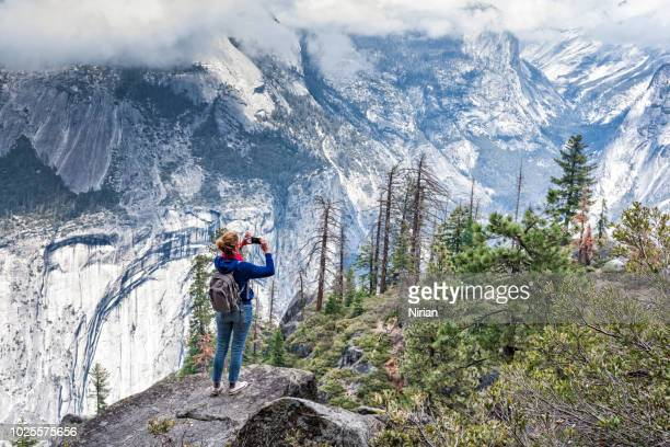 girl  with small backpack taking photo of yosemite - john muir trail stock photos and pictures
